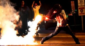 Ferguson Rioter Throws Back Teargas Photo by AP